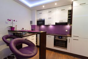 Modern Kitchen With Purple Stools and Accent Wall