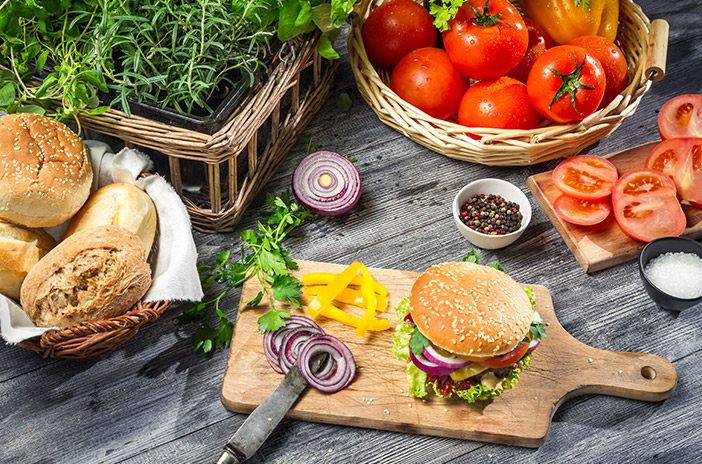 Wooden Table With Burger Bread and Tomatoes