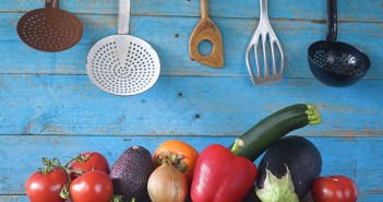 Kitchen Utensils and Vegetables On Blue Background