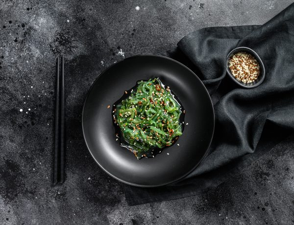 Seaweed salad with sesame seeds in a plate with chopsticks.